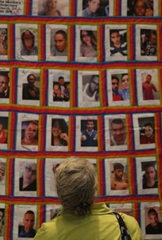 A woman stares at a quilt with the faces of the 49 victims of the Pulse shooting.