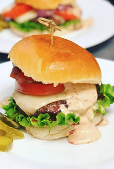 A duck-fat infused beef burger with caramelized onions and Raclette cheese on a brioche bun.