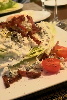 Classic wedge salad topped with bacon lardons and Danish blue cheese.