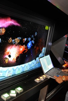 An Imagineer works on Space Mountain's interactive queue