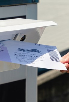 Putting a vote-by-mail ballot in the postbox.