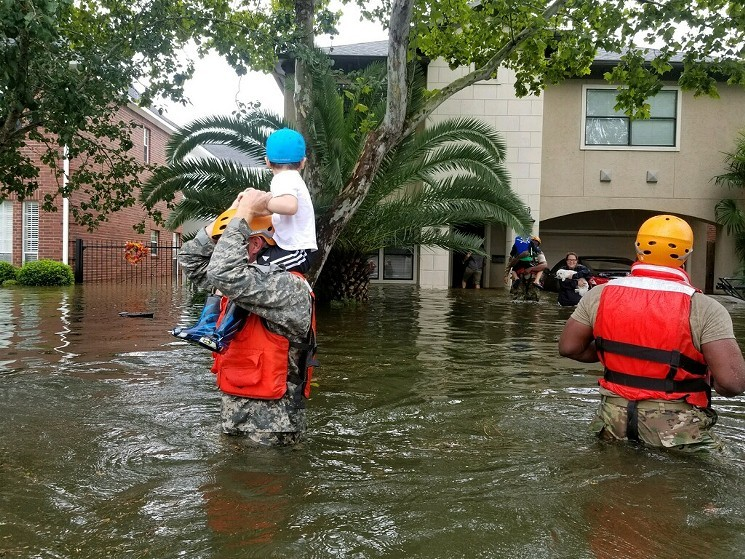 A Houston boy looks at his family Sunday as relief workers carry him to safety. - FLICKR/TEXAS MILITARY DEPARTMENT