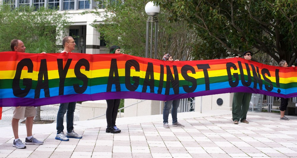 The group Gays Against Guns holds a rainbow banner outside the Orange County courthouse in support of the assault weapons ban. - PHOTO BY MONIVETTE CORDEIRO