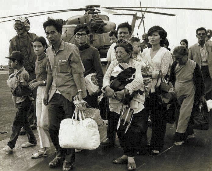 South Vietnamese refugees walk across a U.S. Navy vessel. Operation Frequent Wind, the final operation in Saigon, began April 29, 1975. During a nearly constant barrage of explosions, the Marines loaded American and Vietnamese civilians, who feared for their lives, onto helicopters that brought them to waiting aircraft carriers. - PUBLIC DOMAIN