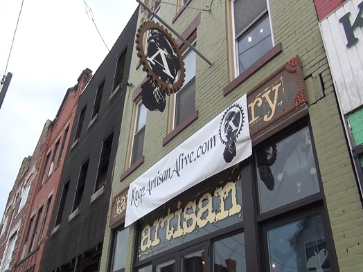 "A banner that reads ""Keep Artisan Alive"" hangs on Artisan Tattoo's facade along Penn Avenue in Garfield. - PHOTO BY ASHLEY MURRAY"
