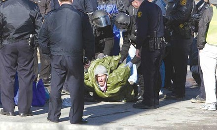 A protester is arrested outside the back entrance to the NREC.