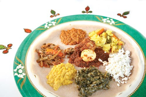 A selection of Ethiopian vegetable and meat entrees, served atop injera - PHOTO BY HEATHER MULL
