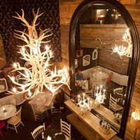 Butcher and the Rye A trendy antler chandelier hangs in the downstairs back dining room. Photo by Heather Mull