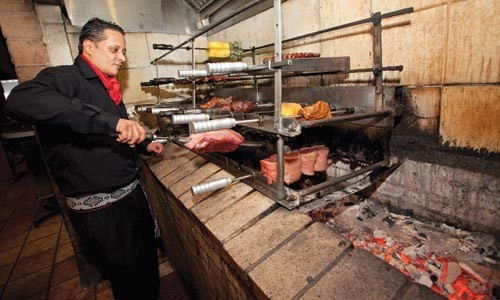 As the meat turns: Carlos Medeiros mans the barbecue. - JOHN ALTDORFER