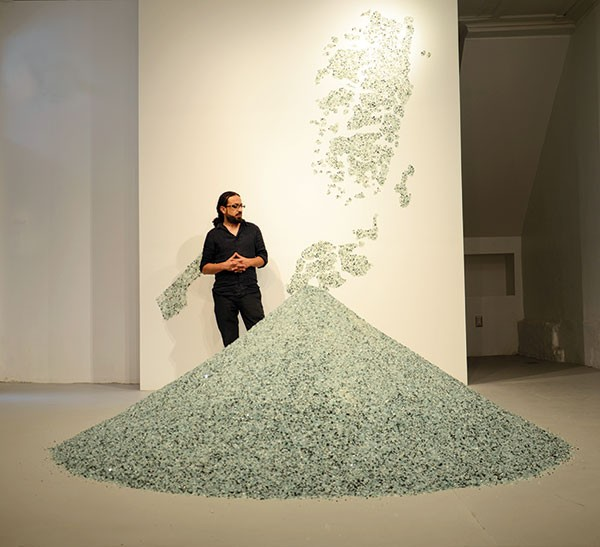 "Bashar Alhroub with his work ""Diamond Land,"" made of broken glass. The map on the wall depicts Palestine."
