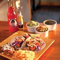 Breaded cod fish tacos, topped with red cabbage, mango salsa and chipotle-Dijon sauce