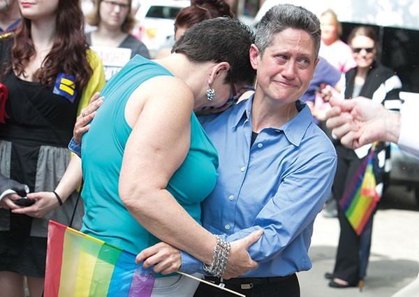 Bystanders react with tears to the Supreme Court's ruling to strike down part of the Defense of Marriage Act during a June 26 rally on Liberty Avenue.