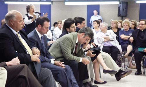 City Councilor Pat Dowd, head in hand, and Mayor Luke Ravenstahl listen to questions about the potential loss of 1,500 jobs at West Penn Hospital. - JOHN ALTDORFER