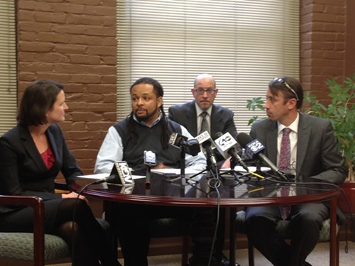 Dennis Henderson (middle) answers questions at an afternoon press conference flanked by his attorneys
