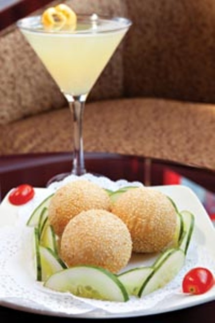 Dim sum sesame-seed balls with an apple-and-cherry tomato garnish, and - a lemontini. - BRIAN KALDORF