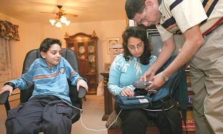Enas (center) and Magdy Habib administer the nightly infusion of a medical solution that provides nutrients their son, Pierre. - PHOTO: HEATHER MULL