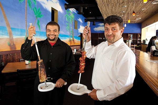 Gauchos Anthony Wannamaker, Jr. (left) and Marchello Giallorenzo (right) serve cuts of roasted meat tableside