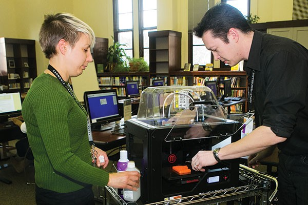Hannah Schilperoort and Wes Roberts of the Carnegie Library use the facility's 3-D printer