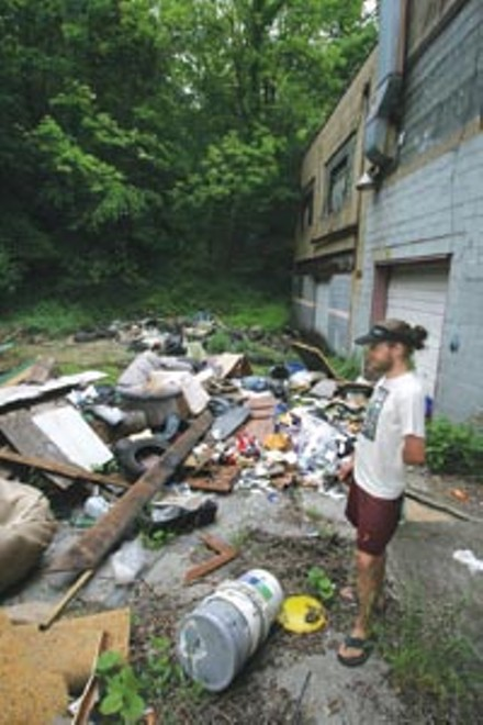 Homewood resident Brian Funk stands amid an illegal dumping ground on Frankstown Avenue. - HEATHER MULL