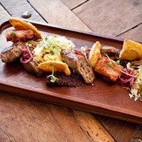 Butcher and the Rye House-made bison sausage and confit wild boar belly, served alongside house-made sauerkraut, potato pirogues, and violet mustard. Photo by Heather Mull