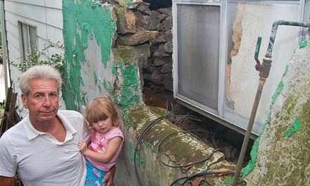 Jack Ingoldsby, with his granddaughter Abby, outside his Ivondale Street home, where the foundation has shifted due to landslides. - DAVID ROMAN