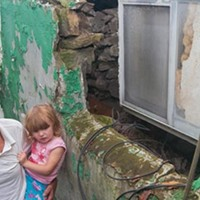 Jack Ingoldsby, with his granddaughter Abby, outside his Ivondale Street home, where the foundation has shifted due to landslides.