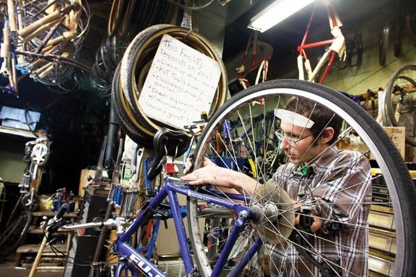 Josh Lane fixes his own bike at Kraynick's Bike Shop. - PHOTO BY RENEE ROSENSTEEL.