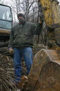 Kurt Rouse, site supervisor for ROAC, Inc., stands next to the mechanical claw of his excavator. - HEATHER MULL