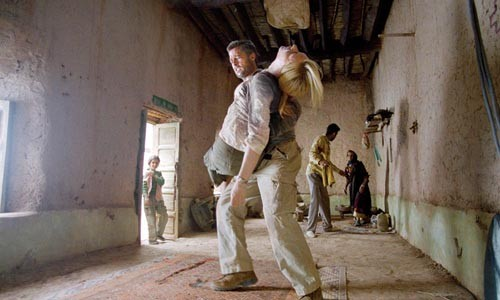Makeshift medic Brad Pitt carries an injured Cate Blanchett