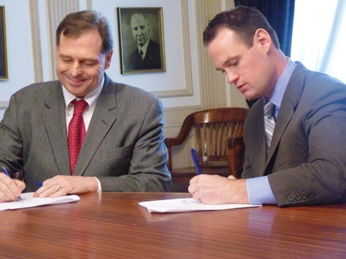 "Mark Flaherty, left, signing a service consolidation agreement with Mayor Luke Ravenstahl in April, says the county should ""get in business"" with Marcellus Shale drillers to see the greatest economic return. - LAUREN DALEY"