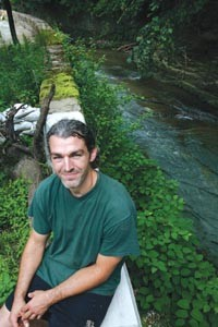 Millvaler Brian Wolovich stands beside a reinforced wall in his backyard. - HEATHER MULL