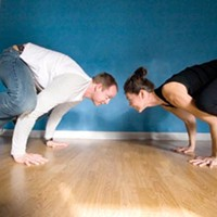 Of a feather: Amazing Yoga owners Sean and Karen Conley do the crow.