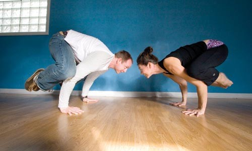 Of a feather: Amazing Yoga owners Sean and Karen Conley do the crow. - PHOTO BY HEATHER MULL