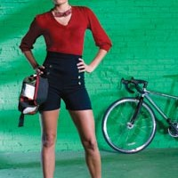 "On Danielle:  ""Mallory Keaton"" red sweater and ""Pin-Up Girl"" shorts, both available from ModCloth.com. Union Jack helmet by Nutcase, available at Biketek. Cycling utility belt, available from fabrichorse.com. ""Arcterra"" sunglasses, by Specialized Optics, and ""Langster"" single-speed road bike, by Specialized, available at Pro Bikes."