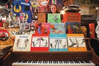 On the record: J. Malls poses in Jerry's Records with some of his collection of vintage album covers by Pittsburgh native Mozelle Thompson.