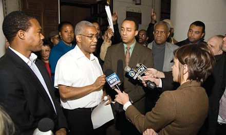One Hill Chairman Carl Redwood answers questions from reporters about the Community Benefits Agreement between the Pittsburgh Penguins and Hill District Community groups. After they were done talking about it, group members burned it. - BRIAN KALDORF