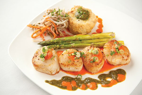 Pan-seared scallops with andouille grit cake, with mirliton slaw and asparagus