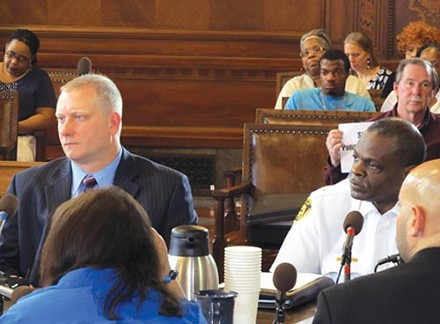 Pittsburgh Public Safety Director Michael Huss, left, and Police Chief Nate Harper discuss their concerns over a proposed police-accountability bill, while Jordan Miles (rear, in blue shirt) looks on. - PHOTO BY CHRIS YOUNG