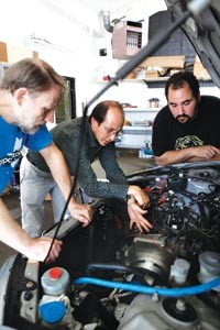 Project scientist Ben Brown (left), Nourbakhsh (center) and researcher Josh Shapiro look under the hood of the Honda Civic that's undergoing a ChargeCar conversion. - HEATHER MULL