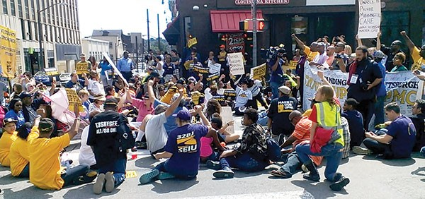 Protesters briefly sat down in the middle of Fifth Avenue and Atwood Street to protest UPMC labor policies.