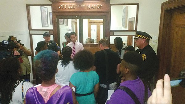 Protesters speak to mayoral staffer Jim Sheppard during a demonstration outside the mayor's office in the wake of the George Zimmerman verdict. - PHOTO BY CHRIS POTTER