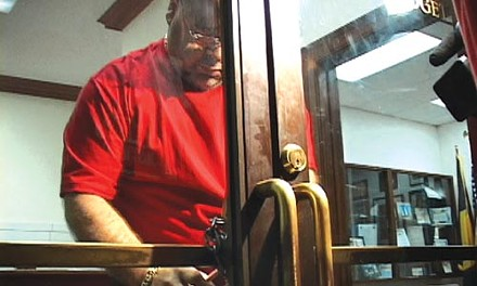 Putting out the welcome mat, Pittsburgh style: With protesters crowded in the hallway outside, a city employee locks the front door to the mayor's office with a chain and padlock. - CHRIS POTTER