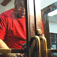 Putting out the welcome mat, Pittsburgh style: With protesters crowded in the hallway outside, a city employee locks the front door to the mayor's office with a chain and padlock.