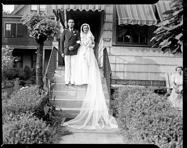 """Roland M. Sawyer and Aileen Eckstein Sawyer posed on their wedding day on steps of The Thimble Shop, 5913 Bryant St., Highland Park, August 1938,"" a photo by Charles ""Teenie"" Harris."