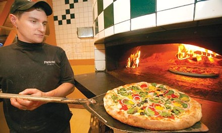 Scott Levin fires up a pizza with spinach, black olives, red onions and banana peppers. - HEATHER MULL
