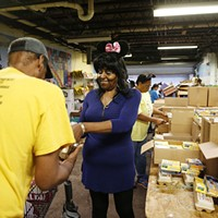 Volunteer Candi Lawrence helps a resident gather items during family pantry day at the Rainbow Kitchen.