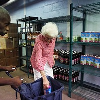 Homestead mayor Betty Esper helps a resident during family pantry day at the Rainbow Kitchen.