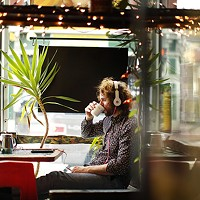 Gary Musisko of Regent Square listens to music in the window at Beehive Coffee.