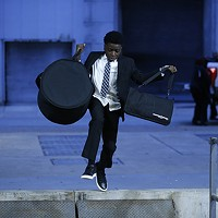 Brandon Terry, drummer for Funky Fly Project, runs and jumps while carrying his drums into the August Wilson Center