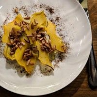 Artichoke topped with sunflower seeds, smoked brined carnival squash, and a dusting of vegetable ash